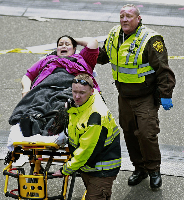 Medical workers aid an injured woman at the finish line of the 2013 Boston Marathon following two explosions there, Monday, April 15, 2013 in Boston. (Photo by Charles Krupa/AP Photo)