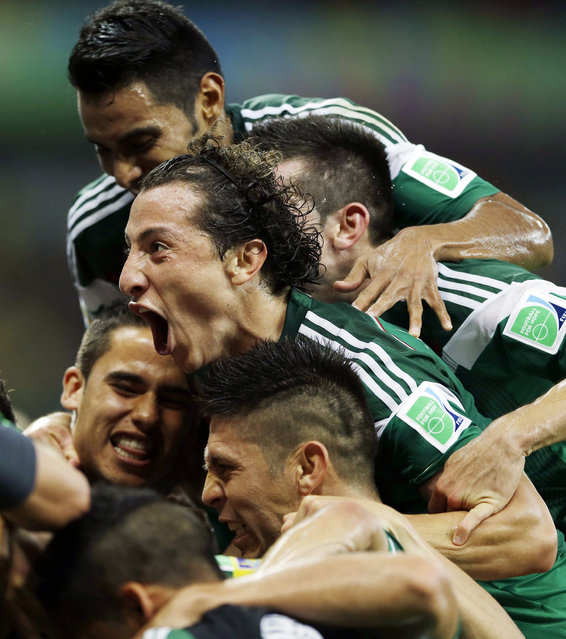 In this June 23, 2014 file photo, Mexico's Andres Guardado celebrates with teammates after Rafael Marquez scored the team's first goal during their World Cup soccer match with Croatia in Recife, Brazil. (Photo by Ricardo Mazalan/AP Photo)