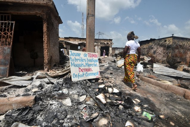 """A resident walks past a sign that reads: """"Youth of Toumodi you burn shops, maquis, markets . Tomorrow, how do we do?"""" that was placed on rubble in the market of Toumodi on November 4, 2020, during a campaign of non-violence and peace awareness by young volunteers after inter-community clashes during the country's presidential election of October 31, 2020. Ivory Coast is caught in a standoff after Ivorian President Alassane Ouattara won a third term by a landslide in October 31, 2020's vote, which was boycotted by the opposition claiming an """"electoral coup"""" in a nation with a constitutional two-term presidential limit. (Photo by Sia Kambou/AFP Photo)"""
