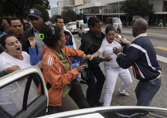 Cuban security personnel detain members of the Ladies in White group during a protest on International Human Rights Day, in Havana December 10, 2014. (Photo by Enrique de la Osa/Reuters)