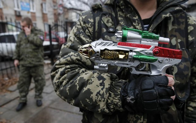 A pro-Russian rebel holds a toy gun in Donetsk December 18, 2014. (Photo by Maxim Shemetov/Reuters)