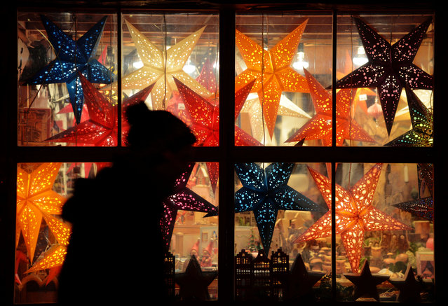 In this Saturday November 29, 2014 picture,  a person passes a window with Christmas decoration in Hannover, northern Germany. (Photo by AP Photo/DPA)