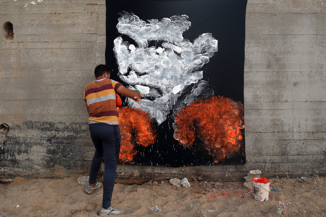 Palestinian artist Osama Sebata, 26, uses boxing gloves to draw a mural of American boxing icon Muhammad Ali in Gaza City on October 20, 2016. (Photo by Mohammed Abed/AFP Photo)
