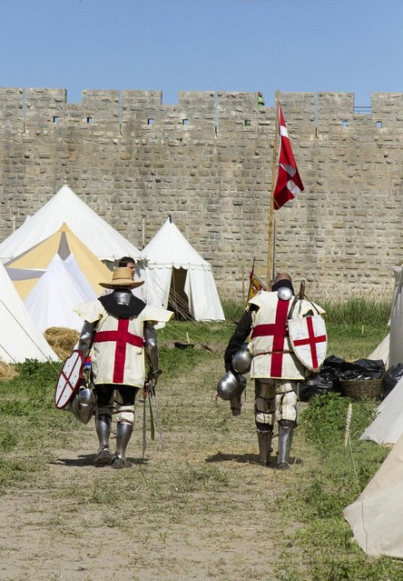 "Members of UK team walk back to their camp during the ""Battle of Nations"" in Aigues-Mortes, southern France, Friday, May 10, 2013 where Middle Ages fans attend the historical medieval battle  competition. The championship will be attended by 22 national teams, which is twice the number it was last year. The battle lasts until May 12. (Photo by Philippe Farjon/AP Photo)"
