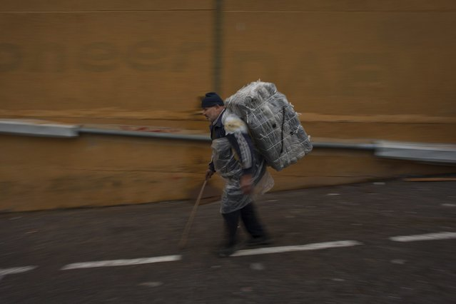 A porter carries a bundle on his back for transport across the El Tarajal boarder separating Morocco and Spain's North African enclave of Ceuta, in Ceuta on December 4, 2014. (Photo by Jorge Guerrero/AFP Photo)