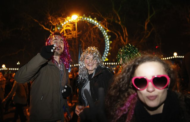 Revellers from London dance as they wait for fireworks to start at the London Eye on the River Thames during New Year's celebrations in London December 31, 2014. (Photo by Suzanne Plunkett/Reuters)