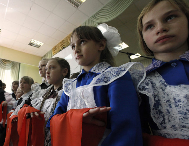 Children, holding red neckerchiefs, a symbol of the Young Pioneer Organisation, salute during a ceremony for the inauguration of 55 newly adopted members on the day of its anniversary at school-lyceum number 12 in Russia's Siberian city of Krasnoyarsk May 19, 2011. (Photo by Ilya Naymushin/Reuters)