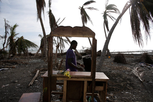A man walks next to a dresser on a beach after Hurricane Matthew in Damassins, Haiti, October 22, 2016. (Photo by Andres Martinez Casares/Reuters)
