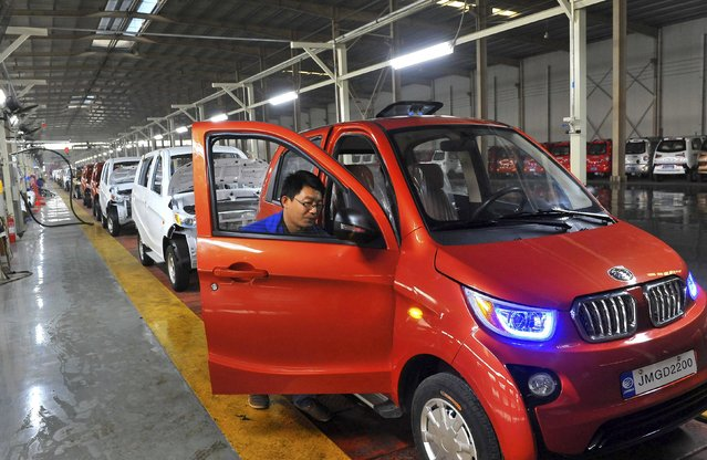 An employee assembles an electric car along a production line at a factory in Qingzhou, Shandong province, China, October 31, 2015. China's factory activity fell for an eighth straight month in October but at a slower pace as export orders flickered into life, a private survey showed on Monday. (Photo by Reuters/China Daily)