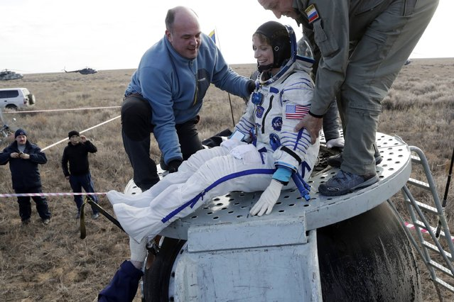 Ground personnel help International Space Station (ISS) crew member US astronaut Kate Rubins to get out of the Soyuz MS space capsule after landing about 150 km (90 miles) southeast of the town of Dzhezkazgan, Kazakhstan, on October 30, 2016. (Photo by Dmitri Lovetsky/AFP Photo)