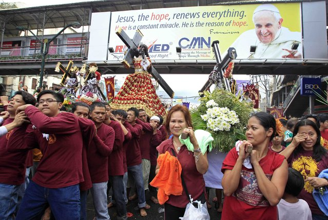 Devotees carrying replica statues of the Black Nazarene walk under a banner of Pope Francis during a procession in Manila January 7, 2015. Millions of devotees are expected to attend the annual procession of the Black Nazarene on Friday. The Black Nazarene, a life-size wooden statue of Jesus Christ carved in Mexico and brought to the Philippines in the 17th century, is believed to have healing powers in the predominantly Roman Catholic country. (Photo by Romeo Ranoco/Reuters)