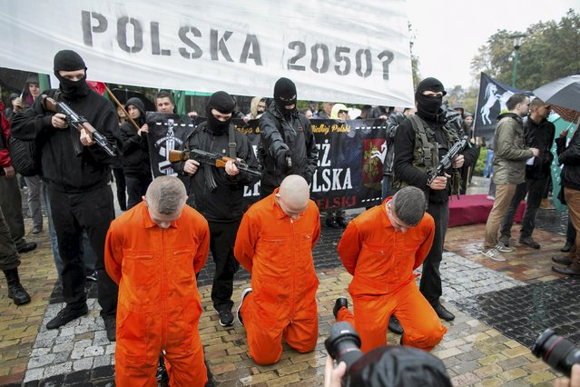 """Participants re-enact a scene of prisoners being shot in the style of Islamic State videos during an anti-migrant demonstration of far-right organizations in Lublin, Poland, September 26, 2015. Banner reads: """"Poland 2050"""". (Photo by Tomasz Rytych/Reuters/Agencja Gazeta)"""