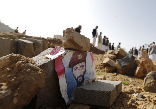 A poster with an image of a soldier lies on his grave after he was killed by al Qaeda militants in the Wadi Hadramout region in northeastern Yemen, at a military cemetery in Sanaa August 10, 2014. (Photo by Khaled Abdullah/Reuters)