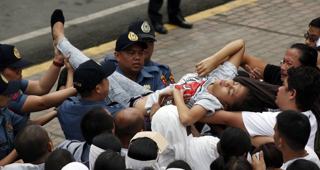 "Policemen carry a woman who become unconscious while waiting for the arrival of Pope Francis outside the Manila Cathedral in Manila January 16, 2015. Pope Francis called on the Philippine government on Friday to tackle corruption and hear the cries of the poor suffering from ""scandalous social inequalities"" in Asia's most Catholic country. (Photo by Erik De Castro/Reuters)"
