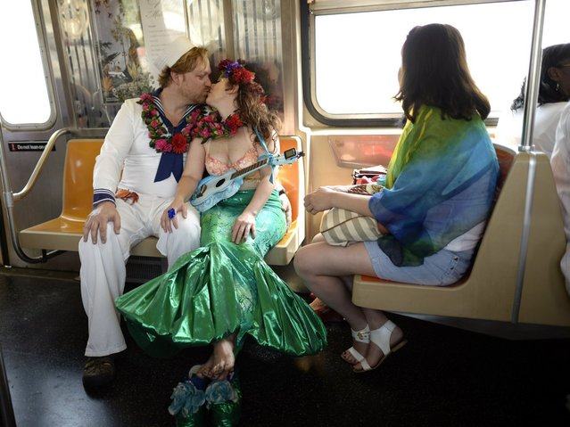 parade participants ride the subway in costume for the 31st Annual Mermaid Parade at New York's Coney Island on June 22, 2103. Over 700,00 people are exptected to turn out for the  scantily clad parade.       AFP PHOTO / TIMOTHY CLARY        (Photo credit should read TIMOTHY CLARY/AFP/Getty Images)