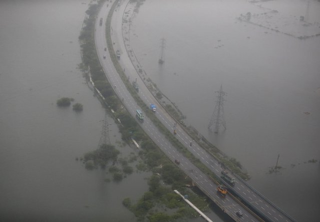 An aerial view shows vehicles moving on roads in a flood-affected area in Chennai, India, December 6, 2015. (Photo by Anindito Mukherjee/Reuters)
