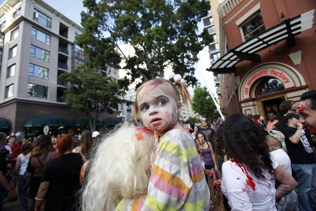 A young girl dressed up as a zombie takes part in a zombie walk in the Gaslamp Quarter during the Comic Con International convention in San Diego, California July 13, 2012. (Photo by Mario Anzuoni/Reuters)