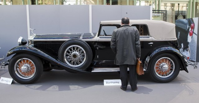 A visitors looks at a Isotta-Fraschini 8A ss cabriolet 1930 displayed by Bonhams auction house, during an exhibition, at the Grand Palais in Paris, Wednesday, February 4, 2015. (Photo by Jacques Brinon/AP Photo)