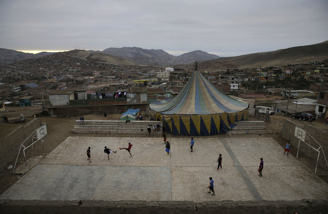 In this July 8, 2018, photo, youths play soccer next to the Tony Perejil circus tent set up in the shantytown of Puente Piedra on the outskirts of Lima, Peru. Urban expansion in the city of 10 million inhabitants makes it tough to find enough space to set up a tent in a centrally located neighborhood, while gangs of delinquents charge up to $10 a day for circuses to set up shop in depressed barrios. (Photo by Martin Mejia/AP Photo)