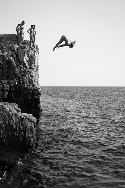 Category winner, open competition, motion. Girl Power, a black-and-white photograph recording the moment when a woman dives off a cliff on the island of Lokrum near Dubrovnik, Croatia, while her friends stand and watch. (Photo by Marijo Maduna/Sony World Photography Awards)