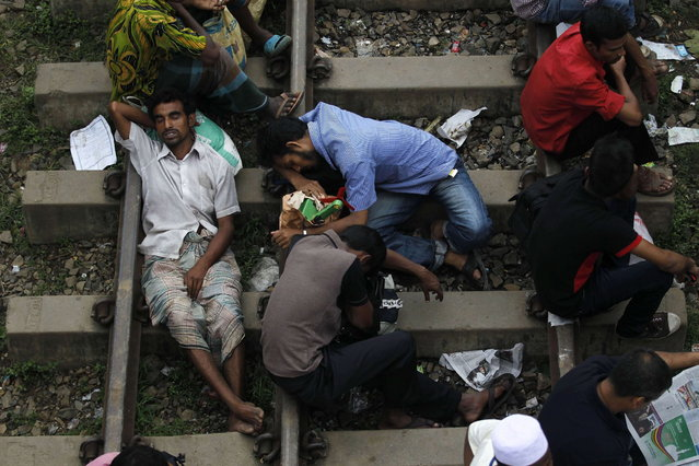 Passengers sleep on a railway track as they wait to board a train at a railway station in Dhaka, August 8, 2013. Millions of residents in Dhaka are travelling home from the capital city to celebrate the Muslim Eid al-Fitr holiday, which marks the end of the holy fasting month of Ramadan. (Photo by Andrew Biraj/Reuters)