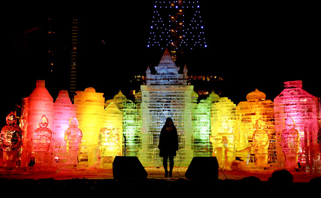 A person stands on stage in front of ice sculptures illuminated at the 66th Sapporo Snow Festival venue at Odori Park in Sapporo, northern Japan, February 5, 2015, the opening day of the mid-winter festival. (Photo by Kimimasa Mayama/EPA)