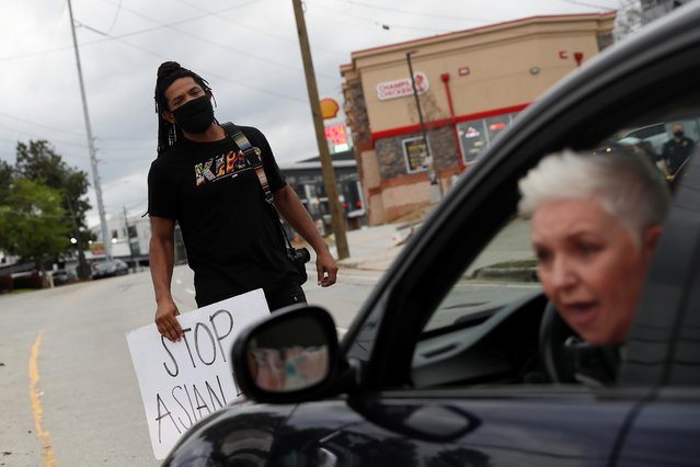 A demonstrator blocks traffic during a rally following the deadly shooting in front of the Gold Spa in Atlanta, Georgia, U.S. March 18, 2021. (Photo by Shannon Stapleton/Reuters)