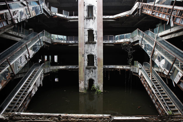 An abandoned department store is seen flooded in Bangkok January 13, 2015. Staff from Bangkok Metropolitan Administration (BMA) office were catching fish at the ground floor of the roofless New World department store that was closed down in 1997. Thousands of fish such as catfish, fancy carps as well as black and red tilapias were released into the ground floor of the building, flooded with rainwater, as local vendors tried to control mosquitoes in the area, local media reported. BMA recently decided to remove the fish and release the water. (Photo by Chaiwat Subprasom/Reuters)
