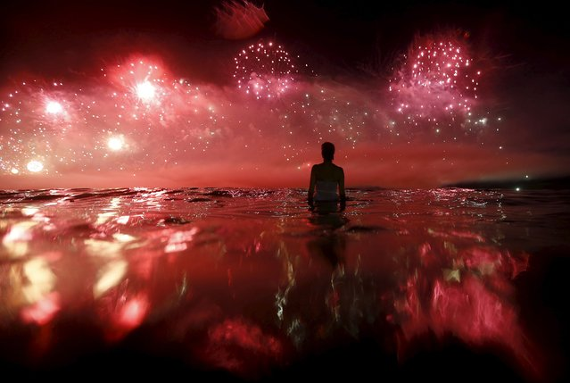 A woman watches as fireworks explode over Copacabana beach during New Year celebrations in Rio de Janeiro, Brazil, January 1, 2016. (Photo by Ricardo Moraes/Reuters)