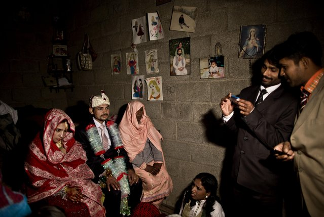 "In this Saturday, February 7, 2015 photo, Pakistani Christian bride Dunya Yacob, 24, and her groom Indriaz Liaqat, 27, sit during their wedding ceremony in a makeshift home at a slum home to Christian families on the outskirts of Islamabad, Pakistan. ""Since I was a little girl, I dreamed of the day I would get married and put on a nice dress and have a nice party with a lot of people"", the 24 year old said. (Photo by Muhammed Muheisen/AP Photo)"