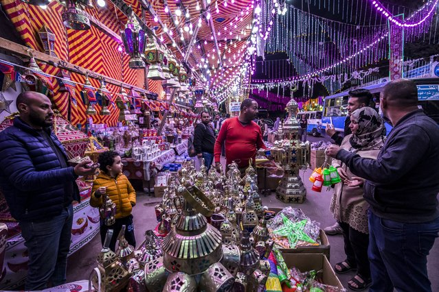 People shop from a stall selling Ramadan lanterns along a main street in the in the northern suburb of Shubra (home to a large Christian population) of Egypt's capital Cairo on April 12, 2021, at the start of the Muslim holy fasting month of Ramadan. (Photo by Khaled Desouki/AFP Photo)