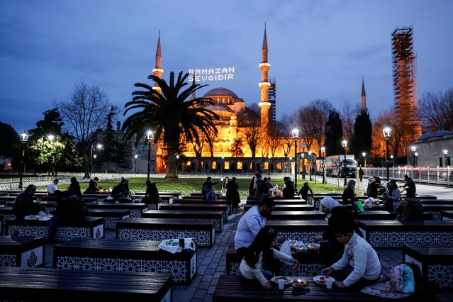 Muslims eat their Iftar (breaking fast) meals in front of the Ottoman-era Sultanahmet mosque, also known as the Blue Mosque, on the first day of Ramadan in Istanbul, Turkey on April 13, 2021. (Photo by Umit Bektas/Reuters)
