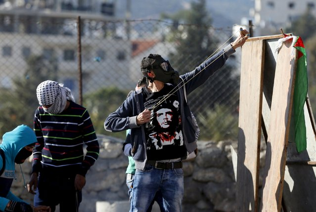 A Palestinian protester uses a slingshot to hurl stones towards Israeli troops during clashes in the West Bank city of Bethlehem January 13, 2016. (Photo by Ammar Awad/Reuters)
