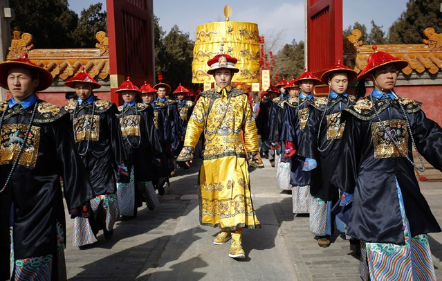 A performer, dressed as a Qing dynasty emperor (C), takes part in a rehearsal of the re-enactment of the ancient Qing Dynasty ceremony, in which emperors prayed for good harvest and fortune for the Chinese New Year celebration, at Ditan Park, also known as the Temple of Earth, in Beijing, February 16, 2015. (Photo by Kim Kyung-Hoon/Reuters)