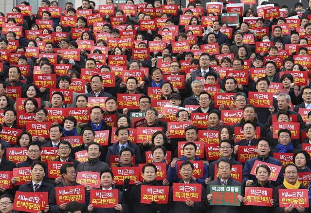 """Lawmakers and members of opposition parties hold cards during a rally demanding the impeachment of South Korean President Park Geun-hye at the National Assembly in Seoul, South Korea, Wednesday, December 7, 2016. Park, who faces impeachment this week, rose to power with the support of conservatives enamored of the economic growth ushered in by her late dictator father decades ago. The sign read """"President Park Geun-hye"""" and """"Impeachment!"""". (Photo by Ahn Young-joon/AP Photo)"""