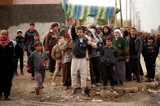 Iraqis gather outside a distribution point run by United Nations agencies at Zahra district, east of Mosul, Iraq December 8, 2016. (Photo by Ahmed Jadallah/Reuters)