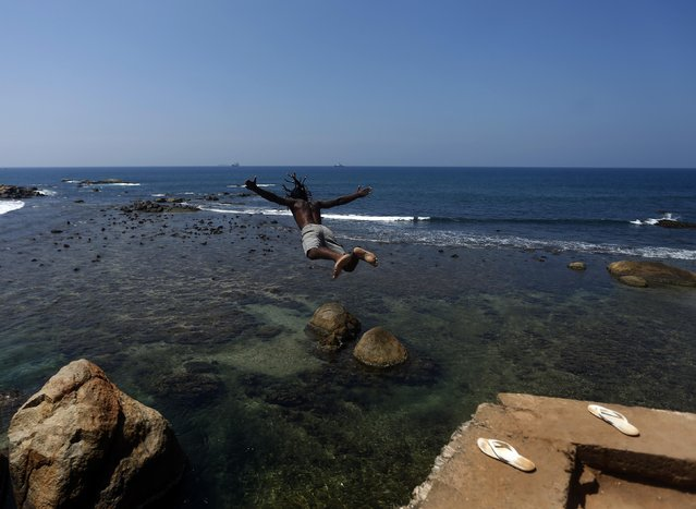 A man jumps into the sea from the top of the Galle Dutch fort in Galle, Sri Lanka February 21, 2015. (Photo by Dinuka Liyanawatte/Reuters)
