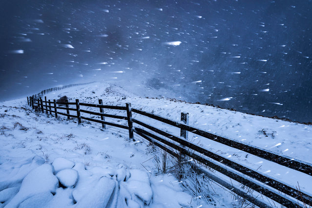 "Blizzard in the High Peak, Derbyshire, by John Finney: ""After a difficult journey in the snow, I made my way from Mam Tor down onto the Great Ridge. As the clouds got darker, I placed the tripod and camera at just the right angle to avoid snow getting onto the lens, and used a flash gun and a relatively slow shutter speed to highlight the fast motion of the blizzard"". Classic view, adult class – winner. (Photo by John Finney/Landscape Photographer of the Year)"