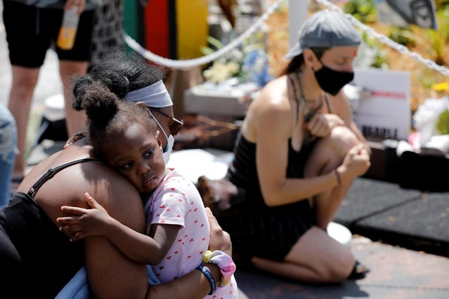 Jacquana Gray embraces her daughter, Olivia, during a moment of silence on the first anniversary of George Floyd's death, at George Floyd Square, in Minneapolis, Minnesota, U.S., May 25, 2021. (Photo by Nicholas Pfosi/Reuters)