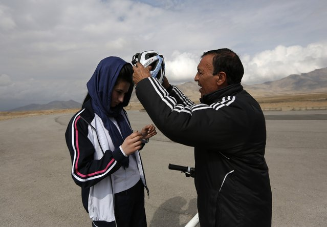 Abdul Sadiq Sadiqi (R), the coach of Afghanistan's Women's National Cycling Team, helps Malika Yousufi during training on the outskirts of Kabul February 20, 2015. (Photo by Mohammad Ismail/Reuters)