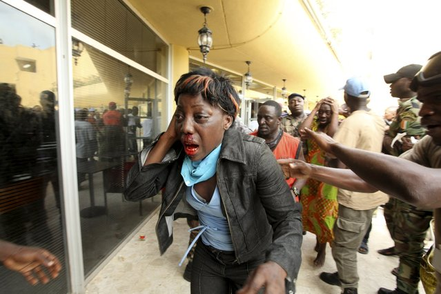 An injured supporter of Ivory Coast's Laurent Gbagbo reacts outside the premises of Hotel Golf, where Gbagbo is currently being held after his arrest, in Abidjan April 11, 2011. (Photo by Reuters/Stringer)