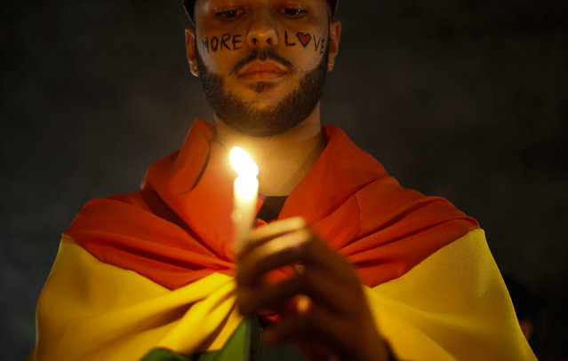 Activists carrying lit candles and flags participate in a vigil to pay tribute to the victims of the massacre occured at a gay club in Orlando, in Sao Paulo, Brazil, on June 15, 2016. (Photo by Miguel Schincariol/AFP Photo)