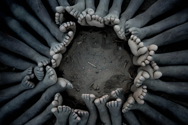 """Ben Moore, December winner. """"The gorgeous little children of the Hamar tribe in southern Ethiopia were only too happy to make this circle of feet for me. They laughed their heads off the whole time"""". MICK RYAN, JUDGE: Maybe a set-up shot, but many are. The most poignant memories of a trip often aren't the grand vistas or the glorious sunrises and sunsets, but the smallest details. These children sitting in a circle and this lovely composition of just their toes, feet and legs, says so much. You decide what. (Photo by Ben Moore/The Guardian)"""