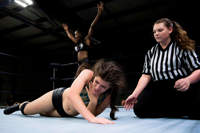 Professional wrestler Gia Scott (L) celebrates after choking Professional wrestler Aria Palmer (C) into submission and winning the match during Autumn Armageddon 2018 in Galena, Maryland on October 6, 2018. (Photo by Jim Watson/AFP Photo)