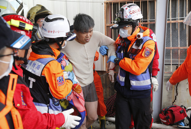 A man is rescued from a collapsed building after an earthquake in Tainan, Taiwan, Saturday, February 6, 2016. (Photo by Wally Santana/AP Photo)