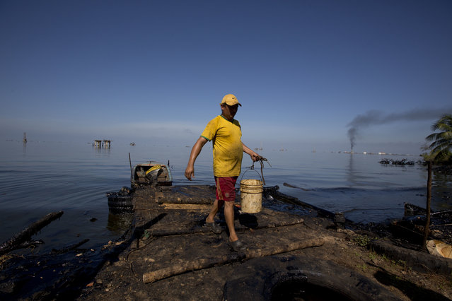 In this August 20, 2018 photo, a fisherman collects water contaminated with oil from Maracaibo Lake in Cabimas, Venezuela. The fisherman will use the water to clean fish. (Photo by Fernando Llano/AP Photo)