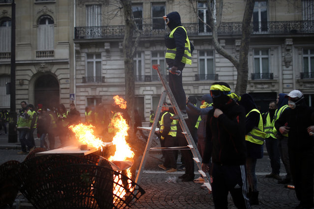 A demonstrator stands on a stepladder during clashes Saturday, December 8, 2018 in Paris. (Photo by Rafael Yaghobzadeh/AP Photo)