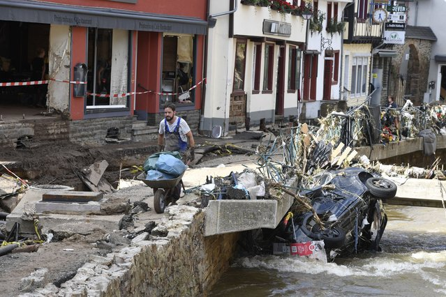 A man helps with the cleanup by carrying rubbish and debris after heavy rain and flooding along the Erft in Bad Münstereifel, Germany, Saturday, July 17, 2021. On the night of July 15, the Erft floods totally devastated the historic core of the city and flooded streets and shops. Gas, electricity and telephone lines were dangerously exposed. (Photo by Roberto Pfeil/dpa via AP Photo)