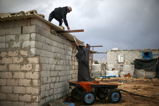 A Palestinian couple fixes their dwelling's roof which is made of sheet metal on a rainy day in Khan Younis in the southern Gaza Strip December 14, 2016. (Photo by Ibraheem Abu Mustafa/Reuters)