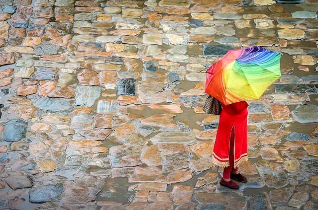 A woman stands under umbrella during rainfall at Bhaktapur Durbar Square, a UNESCO heritage site in Bhaktapur, Nepal on July 14,2021. (Photo by Sunil Sharma/ZUMA Wire/Rex Features/Shutterstock)